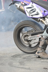At last the race is about to start for this rider. Close up shot with detail in the image (smoke coming from the tyre) as the rider warms the tyre up to get extra grip on the tarmac.